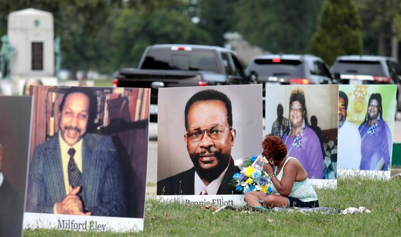 Pictures of Metro Detroit residents who died from the coronavirus line the street during a drive-through memorial, on Belle Isle in Detroit, Michigan, September 1. REUTERS/Rebecca Cook