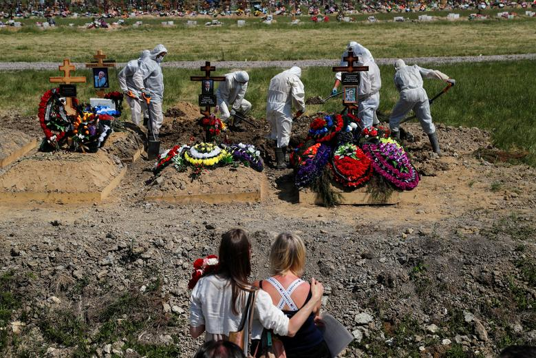 Mourners watch grave diggers burying a person who presumably died of the coronavirus in the special purpose section of a cemetery on the outskirts of Saint Petersburg, Russia, June 26. REUTERS/Anton Vaganov