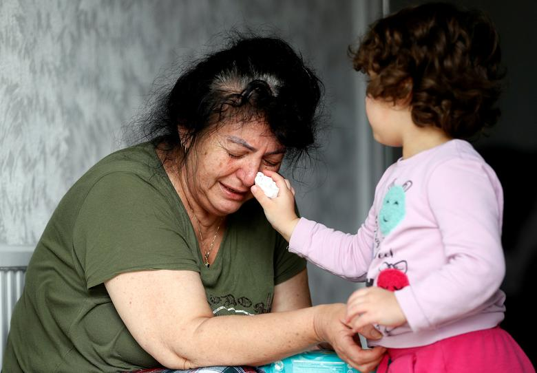 Ayse Mehmet, whose daughter Sonya Kaygan died from the coronavirus, has tears wiped from her face by her three-year-old granddaughter, also named Ayse, at her home in Enfield, Britain, April 27. Kaygan, 26, worked at a nearby care home. REUTERS/Peter Nicholls