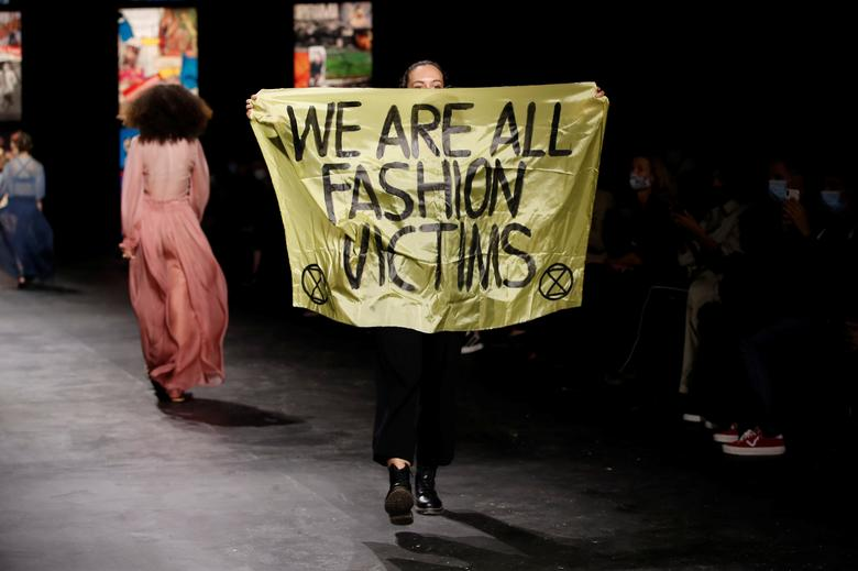 """A woman holds a banner which reads """"We are all fashion victims"""" as she walks on the catwalk during the show by designer Maria Grazia Chiuri for Dior. REUTERS/Benoit Tessier"""