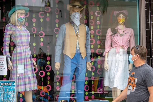 FILE PHOTO: A man wears a mask as he walks past mannequins wearing masks in a retail shopping area during the outbreak of the coronavirus disease (COVID-19) in Encinitas, California, U.S., July 30, 2020.      REUTERS/Mike Blake/File Photo