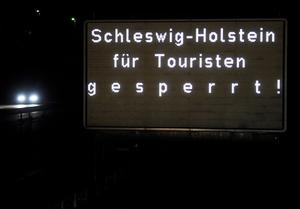 A traffic sign beside a motorway reads