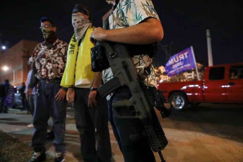 5 Kasım'da Phoenix, Arizona'daki Maricopa İlçe Tabülasyon ve Seçim Merkezi (MCTEC) önünde bir protesto sırasında Başkan Trump'ın destekçileri toplanırken Boogaloo Boys hareketinin bir üyesinin yarı otomatik bir tüfek taşıdığı görülüyor. REUTERS / Jim Urquhart