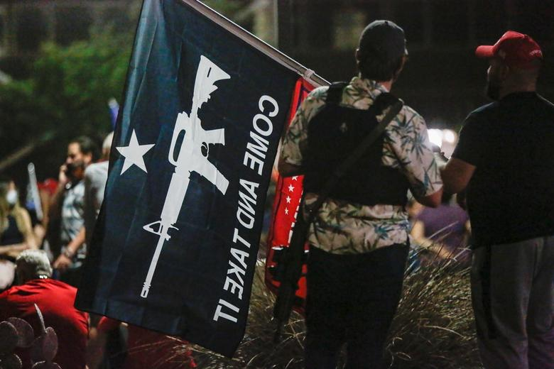 Boogaloo Boys hareketinin bir üyesi, 5 Kasım'da Phoenix, Arizona'daki Maricopa İlçe Tabülasyon ve Seçim Merkezi (MCTEC) önünde bir protestoya katılırken bir bayrak tutuyor. REUTERS / Jim Urquhart