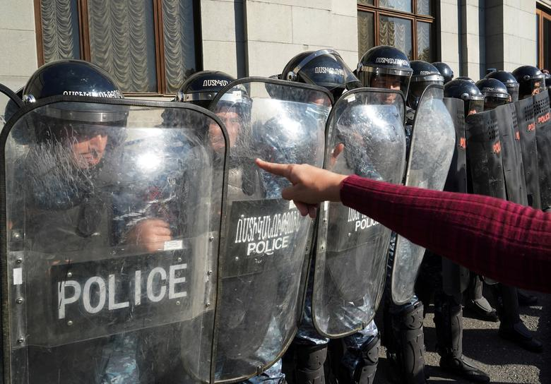 Bir gösterici, Erivan, Ermenistan'da 11 Kasım'da Dağlık Karabağ bölgesindeki askeri ihtilafı sona erdirmek için bir anlaşmanın imzalanmasının ardından Ermenistan Başbakanı Nikol Pashinyan'ın istifasını talep etmek için bir muhalefet mitingi sırasında nöbet tutan kolluk kuvvetlerini işaret ediyor. REUTERS / Artem Mikryukov