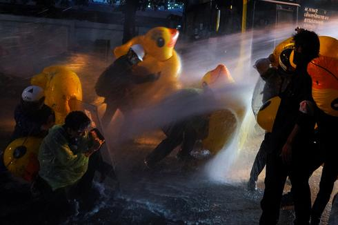 Thai protesters use inflatable ducks against water cannons