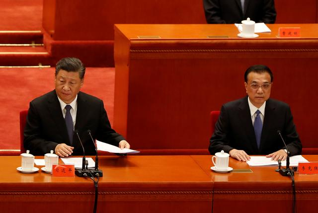 FILE PHOTO: China's President Xi Jinping and Premier Li Keqiang take part in an event marking the 70th anniversary of the Chinese People's Volunteer Army's participation in the Korean War at the Great Hall of the People in Beijing, China October 23, 2020. REUTERS/Carlos Garcia Rawlins