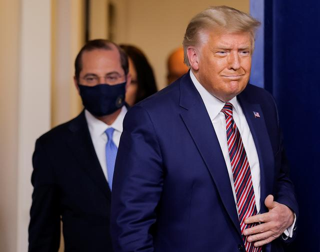 FILE PHOTO: U.S. President Donald Trump is followed by HHS Secretary Alex Azar as he arrives to speak about prescription drug prices during an appearance in the Brady Press Briefing Room at the White House in Washington, U.S., November 20, 2020. REUTERS/Carlos Barria