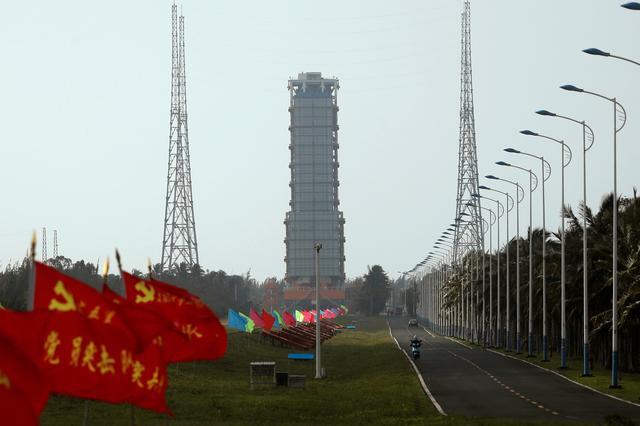 Flags with Chinese Communist Party's emblem flutter along a road leading to a launch tower with the Long March-5 Y5 rocket inside before its launch, at Wenchang Space Launch Center in Hainan Province, China November 23, 2020. REUTERS/Tingshu Wang