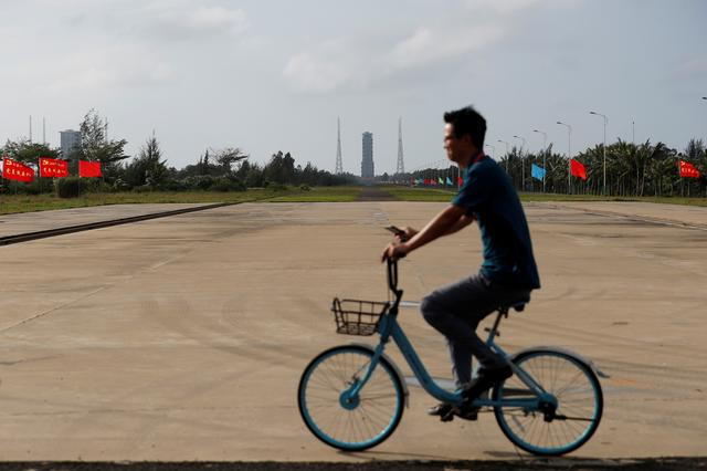 A man rides a bicycle past a rocket launch tower before the launch by the Long March-5 Y5 rocket, at Wenchang Space Launch Center in Hainan Province, China November 23, 2020. REUTERS/Tingshu Wang