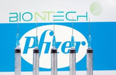 FOTO DE ARCHIVO: Jeringas médicas frente a los logotipos de BioNTech y...