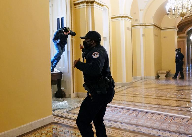 A U.S. Capitol police officer shoots pepper spray at a protestor attempting to enter the Capitol Building in Washington, January 6. Kevin Dietsch/Pool