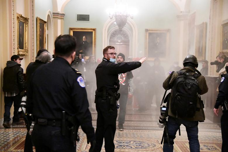 A security officer gestures after supporters of President Trump breached security at the Capitol Building, January 6. REUTERS/Mike Theiler