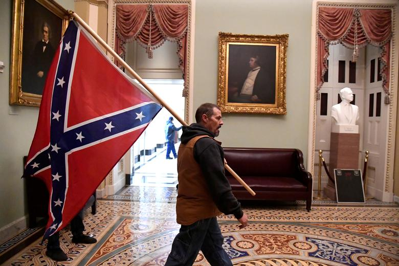 A supporter of President Trump carries a Confederate battle flag on the second floor of the Capitol Building, January 6. REUTERS/Mike Theiler