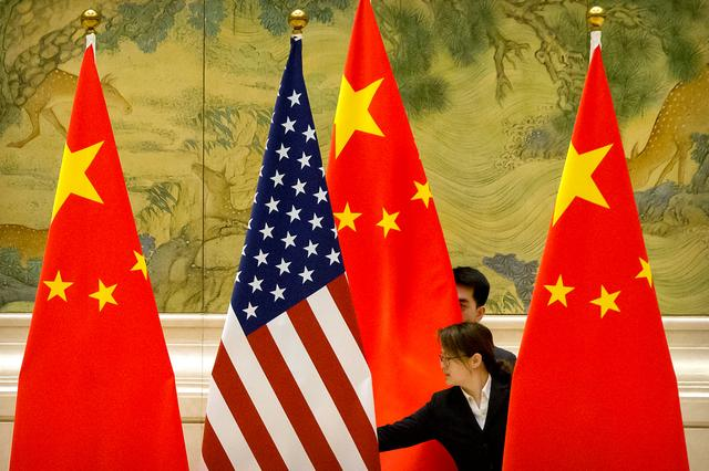 FILE PHOTO: Chinese staffers adjust U.S. and Chinese flags before the opening session of Sino-U.S. trade negotiations in Beijing, Feb. 14, 2019. Mark Schiefelbein/Pool via REUTERS/File Photo