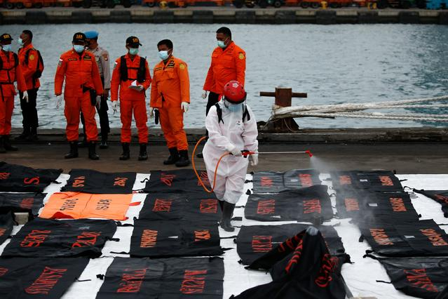 An Indonesian Red Cross worker sprays disinfectant on bags containing body parts of passengers of the Sriwijaya Air flight SJ 182, which crashed into the Java sea, at Tanjung Priok port in Jakarta, Indonesia, January 14, 2021. REUTERS/Willy Kurniawan