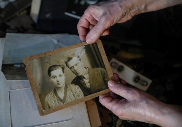 Elizaveta Mikhaylova, a victim of the Soviet mass political repressions known as the Great Terror, shows a photograph of her parents - mother Antonina and Semyon, her father who served a sentence in a forced labour camp and was banned from big cities because of his status, during an interview in her house in the settlement of Zolotkovskiy Razyezd in Vladimir Region, Russia December 22, 2020.  REUTERS/Evgenia Novozhenina