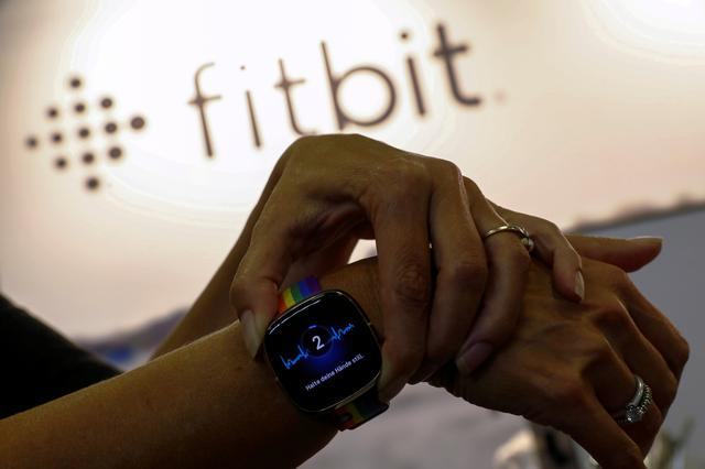 FILE PHOTO: An employee uses an electrocardiogram function on a Fitbit smartwatch at the IFA consumer technology fair, amid the coronavirus disease (COVID-19) outbreak, in Berlin, Germany September 3, 2020. Availability of ECG app pending applicable regulatory clearances including approval under Directive 93/42/EEC (the Medical Device Directive). REUTERS/Michele Tantussi/File Photo