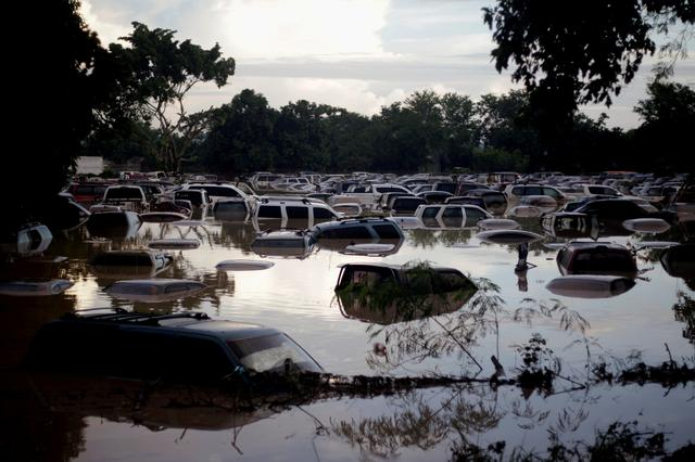 FILE PHOTO: Vehicles are submerged at a plot flooded by the Chamelecon River due to heavy rain caused by Storm Iota, in La Lima, Honduras November 19, 2020. REUTERS/Jorge Cabrera/File Photo