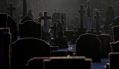 Sunlight hits frost covered headstones in a graveyard amid COVID-19...