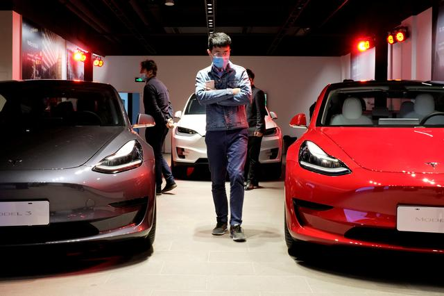 FILE PHOTO: A man wearing a face mask following the coronavirus disease (COVID-19) outbreak walks by Tesla Model 3 sedans and Tesla Model X sport utility vehicle at a new Tesla showroom in Shanghai, China May 8, 2020. REUTERS/Yilei Sun/File Photo