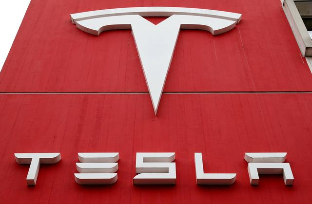 FILE PHOTO: FILE PHOTO: The logo of car manufacturer Tesla is seen at a branch office in Bern, Switzerland October 28, 2020. REUTERS/Arnd Wiegmann