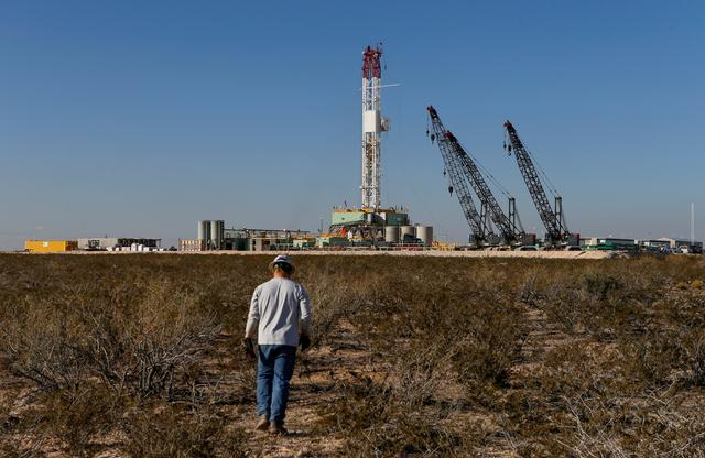FILE PHOTO: An oil worker walks toward a drill rig after placing ground monitoring equipment in the vicinity of the underground horizontal drill in Loving County, Texas, U.S., November 22, 2019. REUTERS/Angus Mordant/File Photo