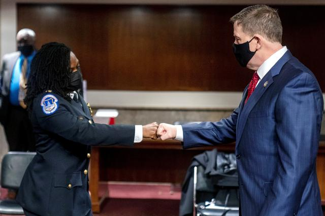Former U.S. Capitol Police Chief Steven Sund, right, and Capitol Police Captain Carneysha Mendoza, left, greet each other before they testify before a Senate Homeland Security and Governmental Affairs & Senate Rules and Administration joint hearing on Capitol Hill, Washington, U.S., February 23, 2021, to examine the January 6th attack on the Capitol. Andrew Harnik/Pool via REUTERS