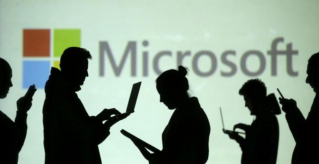 FILE PHOTO: Silhouettes of laptop and mobile device users are seen next to a screen projection of Microsoft logo in this picture illustration taken March 28, 2018.  REUTERS/Dado Ruvic/Illustration
