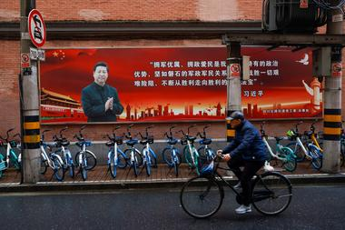 Pictures of Chinese President Xi Jinping overlook a street ahead of the...