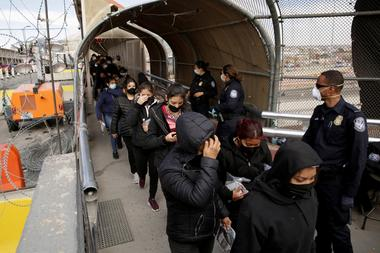 FILE PHOTO: Migrants deported from the U.S. walk towards Mexico at the Paso...
