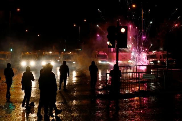 Rioters look on as fireworks go off near the police vehicles on the Springfield Road as protests continue in Belfast, Northern Ireland April 8, 2021. REUTERS/Jason Cairnduff