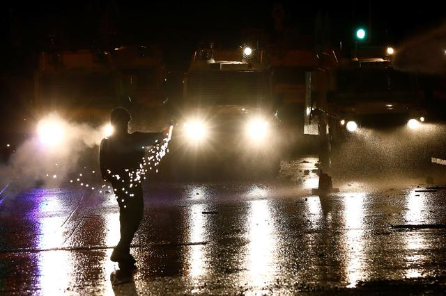 A rioter throws an object at the police on the Springfield Road as protests continue in Belfast, Northern Ireland April 8, 2021. REUTERS/Jason Cairnduff