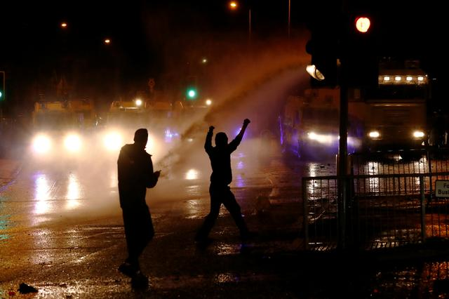 Rioters react as the police uses a water cannon on the Springfield Road as protests continue in Belfast, Northern Ireland April 8, 2021. REUTERS/Jason Cairnduff