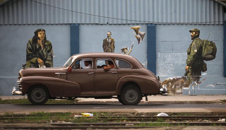 Ein Oldtimer fährt an einem Wandgemälde vorbei, das Kubas ehemaligen Führer Fidel Castro, Nationalheld Jose Marti und Revolutionsführer Che Guevara in Havanna zeigt, August 2009. | Bildquelle: REUTERS | Bilder sind in der Regel urheberrechtlich geschützt