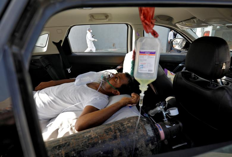 A patient with breathing problems lies inside a car while waiting to enter a COVID-19 hospital for treatment in Ahmedabad, April 22. Health officials across northern and western India including the capital, New Delhi, said they were in crisis, with most hospitals full and running out of oxygen. REUTERS/Amit Dave
