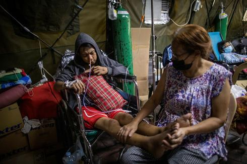 Relatives care for COVID-stricken loved ones in overcrowded Manila hospital
