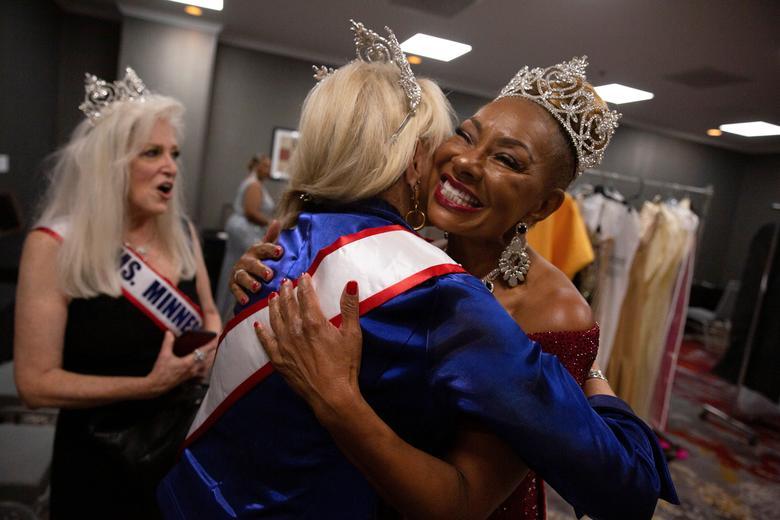 Ms. Oklahoma Senior America 2021 Kathryn Gordon hugs Ms. Texas Senior America 2019/20 Joyce Brown in the dressing room before the pageant. REUTERS/Shelby Tauber