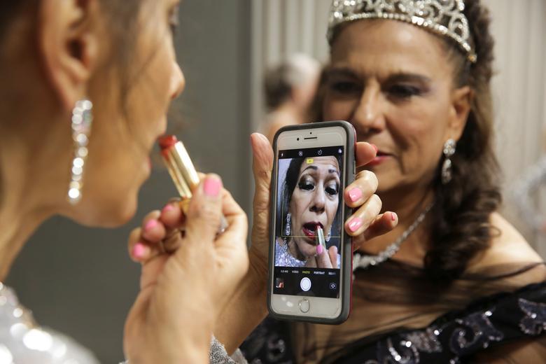 Nina Elizalde Crocker puts on lipstick before a group photo. REUTERS/Shelby Tauber