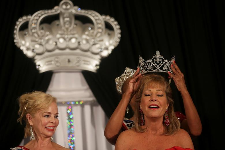 Joyce Brown places the crown on Kimberly Ghedi, the newly appointed Ms. Texas Senior America 2022. REUTERS/Shelby Tauber