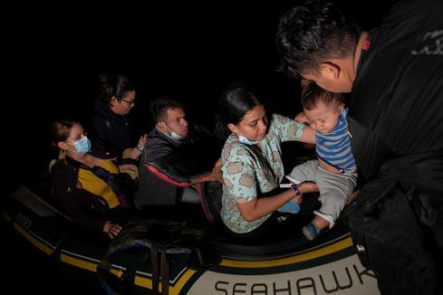 Asylum-seeking migrants cross Rio Grande under cover of darkness