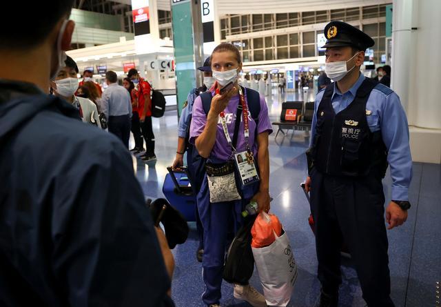 Belarusian sprinter Krystsina Tsimanouskaya is escorted by police officers at Haneda international airport in Tokyo, Japan August 1, 2021.  REUTERS/Issei Kato