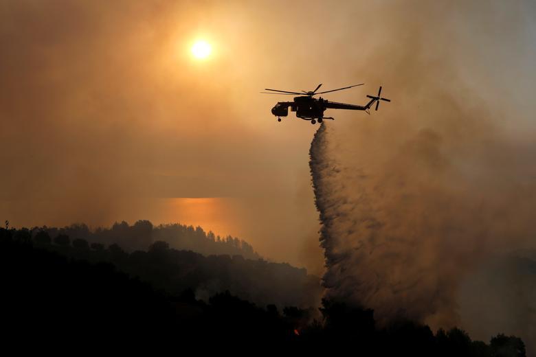 Yunanistan, Patras yakınlarındaki Ziria köyü yakınlarında orman yangını yanarken bir yangın söndürme helikopteri su damlası yapıyor, 1 Ağustos 2021. REUTERS/Costas Baltas