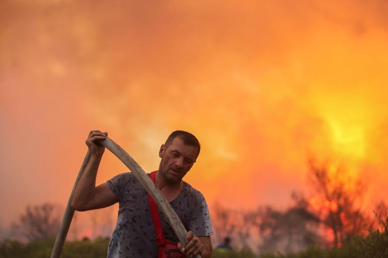 Yunanistan'ın Atina kentinin kuzeyindeki Varympompi banliyösünde çıkan orman yangını sırasında gönüllü bir itfaiyeci hortum tutuyor, 3 Ağustos 2021. REUTERS/Giorgos Moutafis
