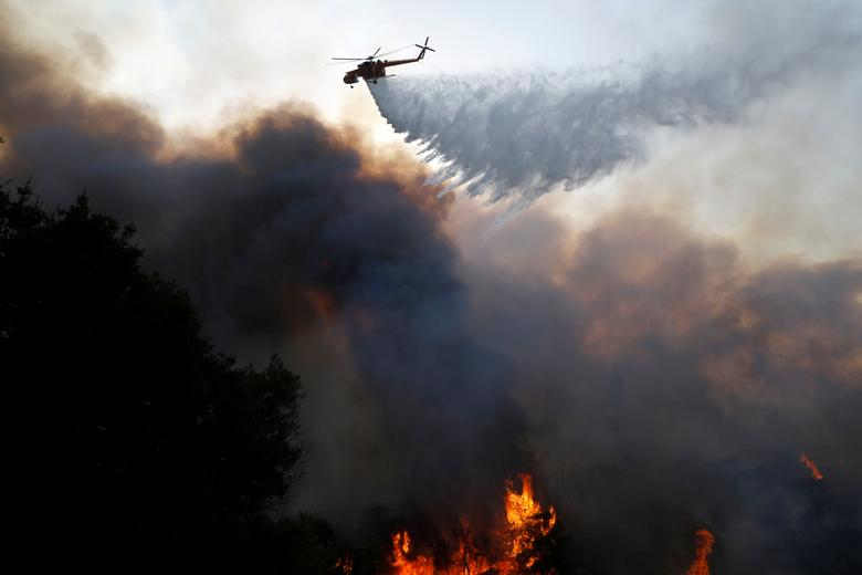 Atina'nın kuzeyindeki Varympompi banliyösünde bir yangın söndürme helikopteri su damlası bırakırken, Yunanistan, 3 Ağustos 2021. REUTERS/Costas Baltas