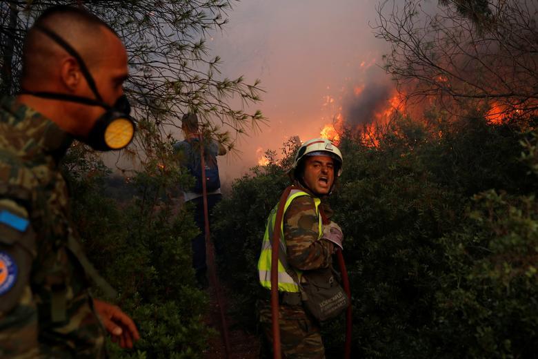 Gönüllü itfaiyeciler Yunanistan'ın Atina kentinin kuzeyindeki Varympompi banliyösünde çıkan orman yangınını söndürmeye çalışıyor, 3 Ağustos 2021. REUTERS/Costas Baltas