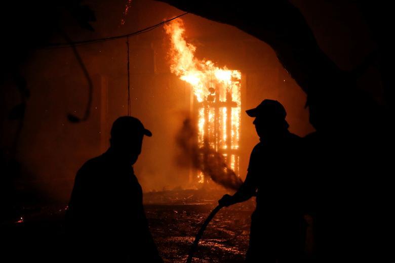 Atina'nın kuzeyindeki Nea Kifisia banliyösünde 3 Ağustos 2021'de çıkan yangın sırasında insanlar yanan bir evi söndürmeye çalışıyorlar. REUTERS/Costas Baltas