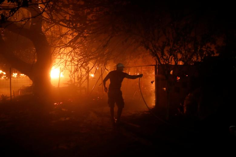 Atina'nın kuzeyindeki Nea Kifisia banliyösünde 3 Ağustos 2021'de çıkan bir orman yangını sırasında bir adam ağaç gövdesindeki yangını söndürmeye çalışıyor. REUTERS/Costas Baltas
