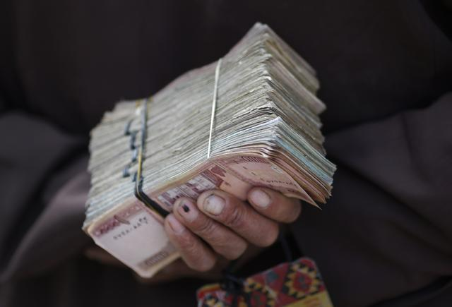 FILE PHOTO: A money changer holds a stack of Afghan currency on a street in central Kabul April 2, 2014. REUTERS/Tim Wimborne