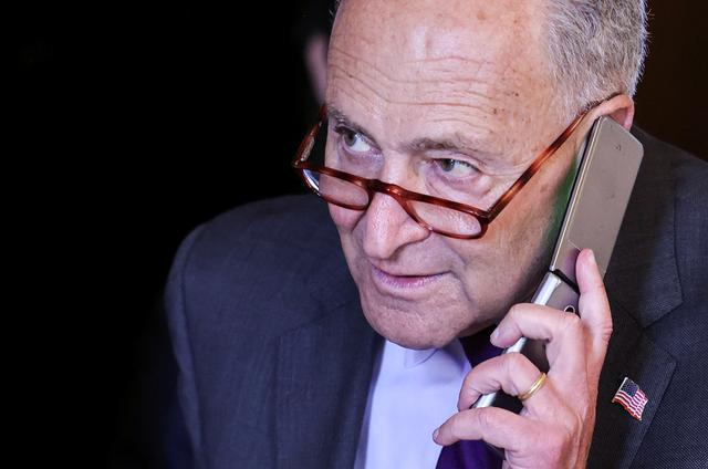 U.S. Senate Majority Leader Chuck Schumer (D-NY) talks on a phone as he departs following the weekly Senate Democratic policy lunch at the U.S. Capitol in Washington, U.S., September 14, 2021. REUTERS/Evelyn Hockstein